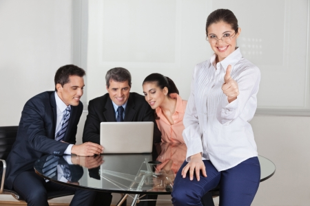 Smiling businesswoman holding her thumbs up with team in the background Stock Photo - 16166256