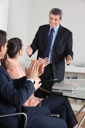 Manager clapping hands for consultant after a presentation in the office 版權商用圖片