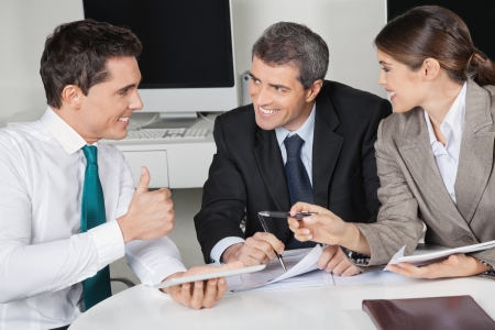 Happy manager in business meeting holding his thumb up Stock Photo - 16166195