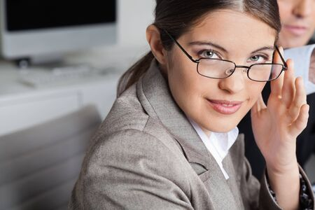 farsighted: Attractive smiling business woman with glasses sitting in the office