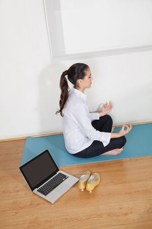 Relaxed businesswoman meditating in office during her lunch break photo