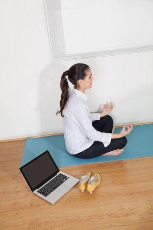 break in: Relaxed businesswoman meditating in office during her lunch break