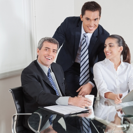 Smiling business team sitting at a conference table for a meeting Stock Photo - 16166251