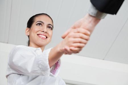 the farewell: Apretón de manos con una mujer de negocios sonriente en la oficina