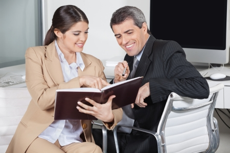 appointment book: Two smiling business people looking in an appointment book in the office
