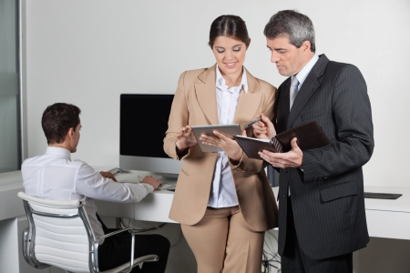 Business people making appointments with tablet pc and datebook photo