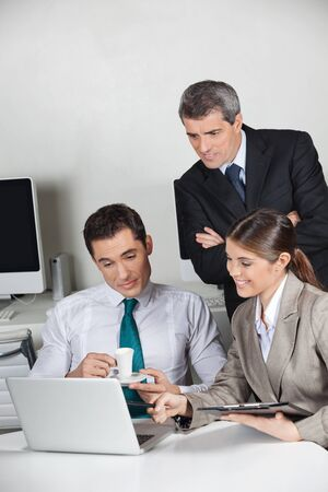 Three business people working together at laptop computer in the office Stock Photo - 16253747