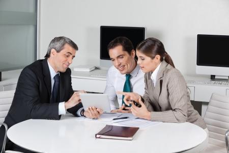 agente comercial: Empresas asesor fiscal con el ordenador tableta en una reunión en la oficina