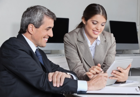 advocate: Secretary and businessman doing time management with tablet pc in the office
