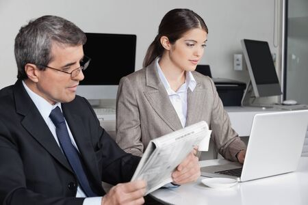 Business woman working with laptop and man reading newspaper in the office Stock Photo - 16253760
