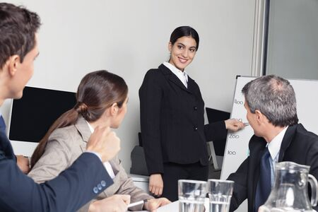 Smiling business woman giving a sales presentation for her team in the office photo