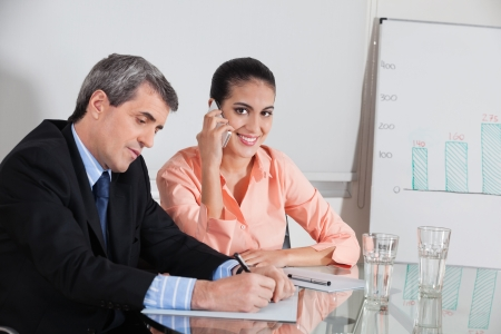 Business woman making a call in a meeting while a manager takes notes photo