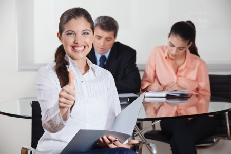 likeable: Happy busines woman with files in office holding her thumbs up