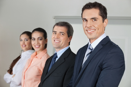 Row of four happy businesspeople in the office photo