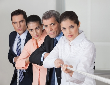 Serious business people team playing tug of war in the office photo