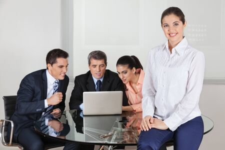 Happy attractive business woman with her team around a laptop in the office photo