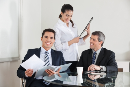Three happy businesspeople working together in the office photo