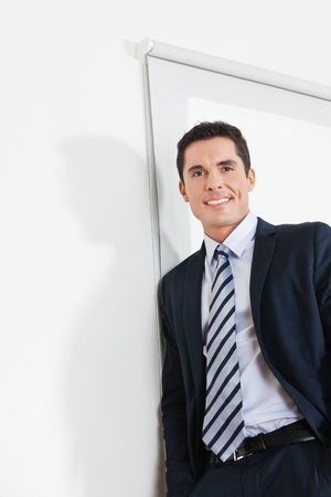 Portrait of an attractive businessman leaning on a white office wall photo