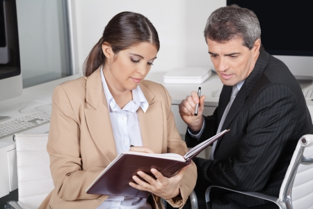 Female assistent checking appointments for manager in datebook photo