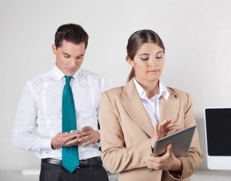 Two businesspeople checking data exchange between tablet pc and smartphone photo
