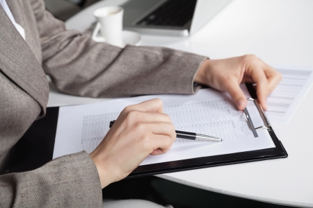 examiner: Hand of a businesswoman at her desk with a pen and a clipboard