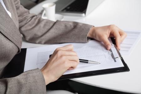 inventario: La mano de una mujer de negocios en su escritorio con una pluma y un portapapeles Foto de archivo