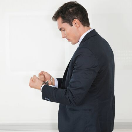 Manager in handcuffs in his office looking sad Stock Photo - 16253731