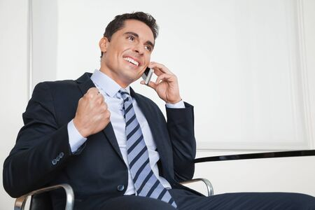 listen fist: Cheering happy businessman with smartphone clenching his fist