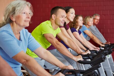 overweight people: Spinning class exercising in a fitness center Stock Photo