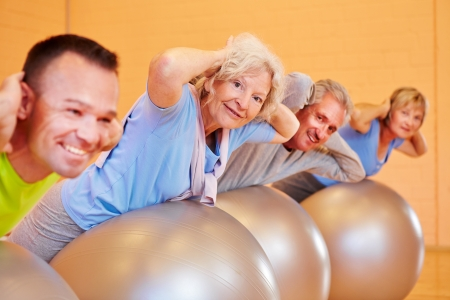 Elderly group doing back exercises in a fitness center photo