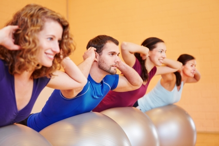 back exercise: Young group doing gymnastics in fitness center on gym balls