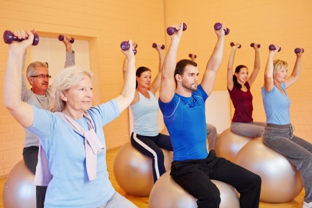 senior citizens: Group in fitness center doing dumbbell training sitting on gym balls