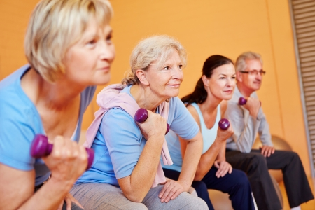 Group of elderly people doing senior sports in fitness center with dumbbells Stock Photo