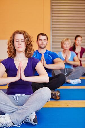 Yoga course with men and women meditating in a fitness center photo