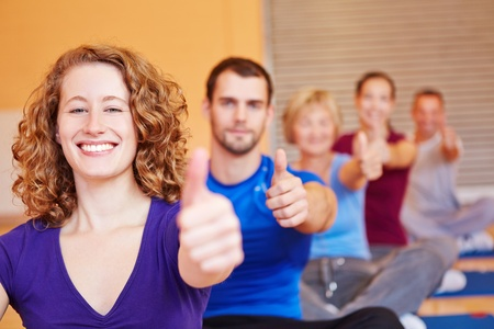 Happy attractive woman in fitness center holding her thumbs up photo