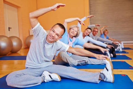 health club: Senior sports class doing stretching exercises in a health club Stock Photo