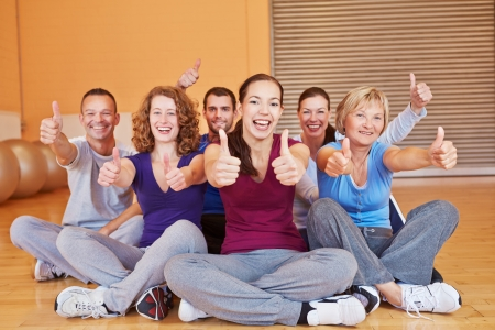 Happy smiling group in fitness center holding their thumbs up in a gym Foto de archivo