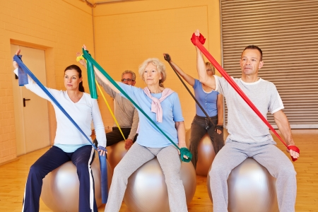 Senior people in gym doing back training with exercise band photo