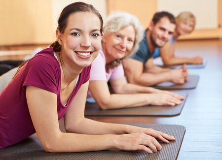 aerobic training: Smiling group exercising together in a fitness center Stock Photo