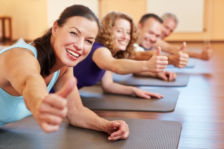 back exercise: Happy senior woman in fitness class in a health club holding her thumbs up Stock Photo