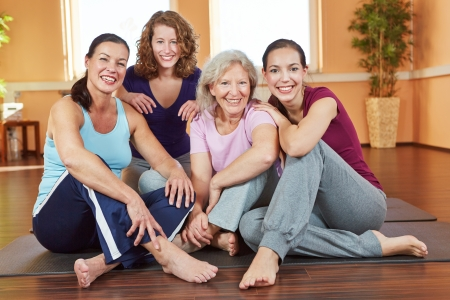 group of women: Portrait of four smiling happy women sitting in a fitness center