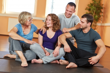 Smiling group with men and women talking in a fitness center photo