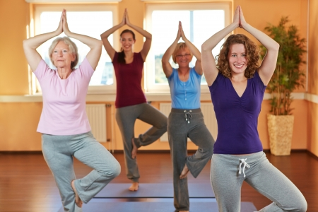 health club: Happy group of women in yoga class in health club Stock Photo