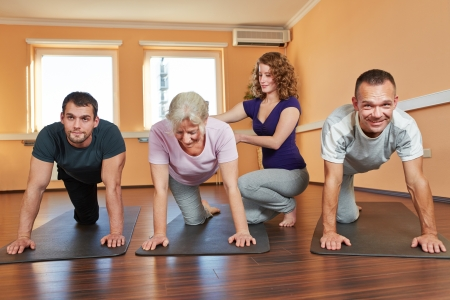 back exercise: Group doing senior sport with instructor in fitness center Stock Photo
