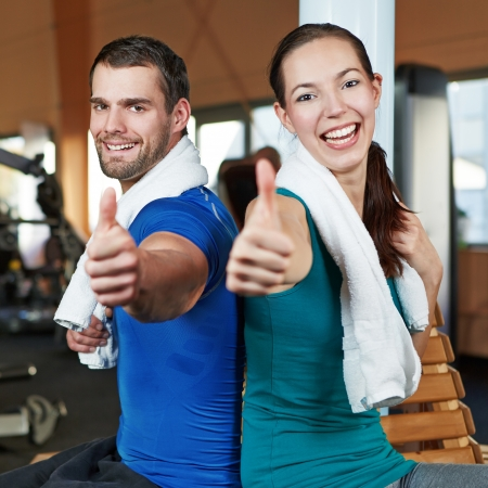 fitness club: Smiling happy couple holding their thumbs up in a fitness center