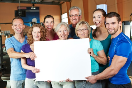 training course: Big happy group holding empty white poster in fitness center