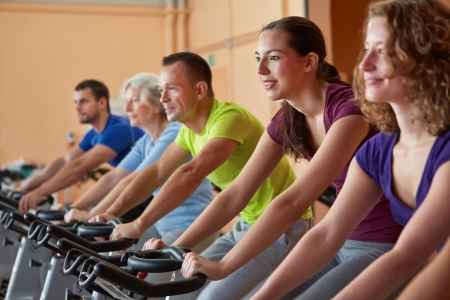 Mixed group riding bikes in spinning class in fitness center photo
