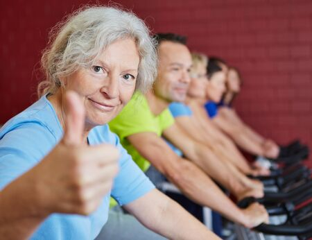 people laughing: Smiling senior woman holding her thumbs up in spinning class in a fitness center Stock Photo