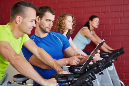 training programs: Fitness trainer with clipboard talking to a man on spinning bike