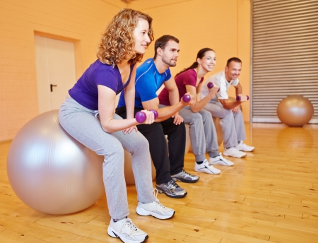 fitnesscenter: Young people in back training class in a fitnesscenter with dumbbells